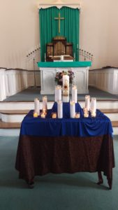 Organ in background and table with candles in foreground